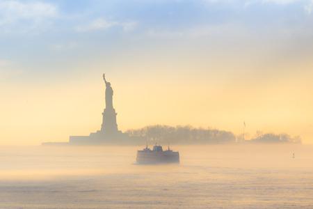 Staten Island Ferry Fahrten vorbei an der Freiheitsstatue auf einem nebelhaften Sonnenuntergang. Manhattan, New York City, Vereinigte Staaten von Amerika.