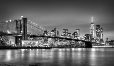 Brooklyn-Brücke und New York City Manhattan Skyline in der Abenddämmerung mit Wolkenkratzern über den East River panorama beleuchtet. Kopieren Sie Platz. Schwarzweiss-Bild.
