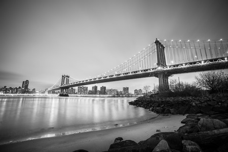 manhattan bridge: Manhattan bridge and New York City downtown skyline at dusk with skyscrapers illuminated over East River panorama. Copy space. Black and white image. Stock Photo