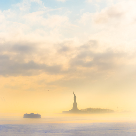 liberty island: Staten Island Ferry cruises past the Statue of Liberty on a misty sunset. Manhattan, New York City, United States of America. Square composition. Copy space.
