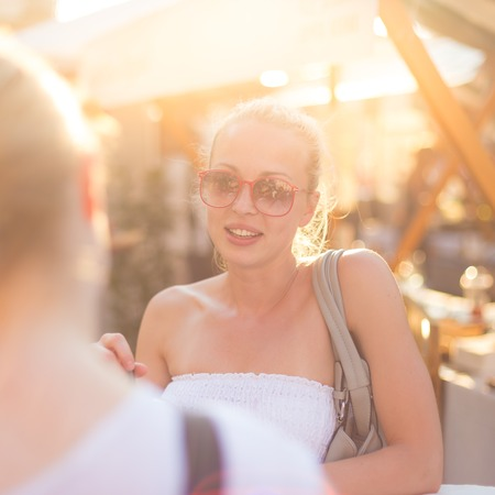 after to work: Es bueno verte. Ha pasado un tiempo. Dos felices j�venes amigas goza de una conversaci�n en el mercado de alimentos en las ciudades al azar despu�s del encuentro de trabajo. Agradable socializaci�n tiempo libre. Foto de archivo