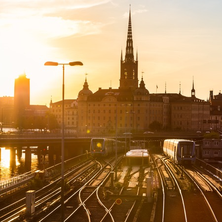 norrmalm: Railway tracks and trains near Stockholms main train station in Norrmalm area, Stockholm, Sweden in sunset.  Silhouette of city hall and cathedral in background. Square composition.