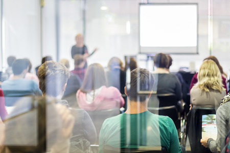 onderwijs: Speaker Het geven van een Talk op zakelijke bijeenkomst. Publiek in de conferentiezaal. Bedrijfsleven en ondernemerschap. Via de glazen deur kijken.