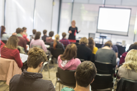 academics: Speaker giving presentation in lecture hall at university. Participants listening to lecture and making notes.  Trough the glass rear view of audience in lecture room. Stock Photo