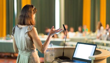 Vrouwelijke spreker op Business Conference en presentatie. Publiek bij de conferentiezaal. Bedrijfsleven en ondernemerschap. Zakenvrouw. Horizontale samenstelling.