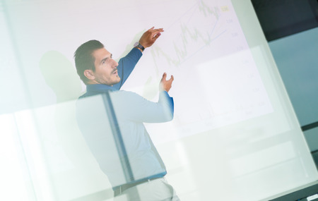 training business: Business man making a presentation in front of whiteboard. Business executive delivering a presentation to his colleagues during meeting or in-house business training. View through glass.
