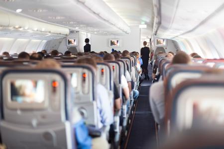 Intérieur de gros avion de passagers avec des personnes sur les sièges et hôtesse de l'air en uniforme marchant dans l'allée.