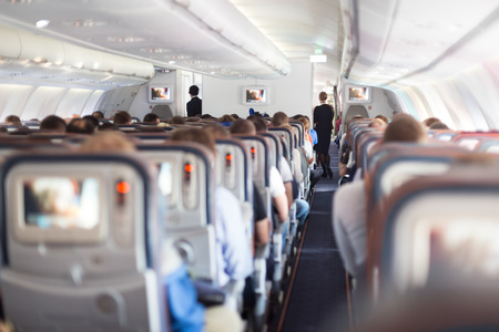 Interior of large passengers airplane with people on seats and stewardess in uniform walking the aisle. Stockfoto