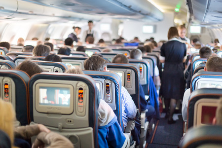 Interior of large passengers airplane with people on seats and stewardess in uniform walking the aisle. Stock Photo