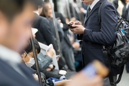 Interior of moder Tokyo metro with passengers on seats and businessmen using their cell phones. Corporate business people commuting to work by public transport. Horizontal composition. Standard-Bild