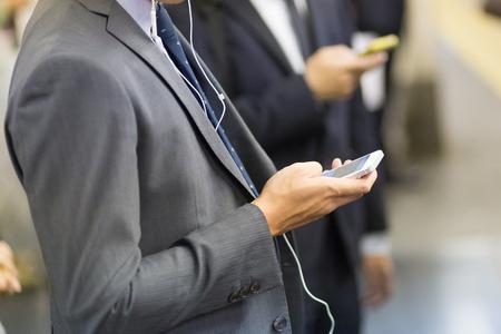 hombre de negocios: Los hombres de negocios que utilizan sus teléfonos celulares en el metro de Tokio. Composición horizontal. Foto de archivo