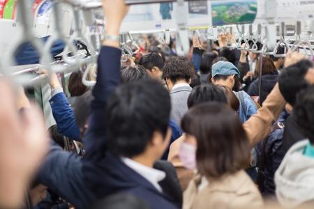 Die Passagiere von Tokyo Metro reisen. Geschäftsleute, die das Pendeln mit öffentlichen Verkehrsmitteln in der Hauptverkehrszeit zu arbeiten. Geringe Schärfentiefe Foto. Horizontale Zusammensetzung.
