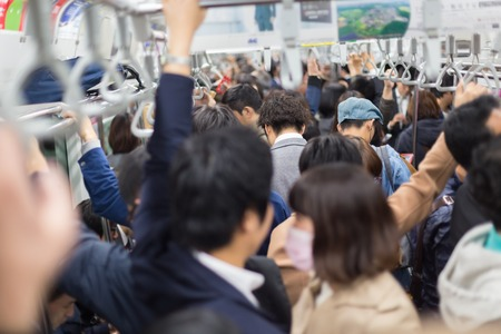 doprava: Passengers traveling by Tokyo metro. Business people commuting to work by public transport in rush hour. Shallow depth of field photo. Horizontal composition.