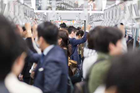 Passagiers die met de metro van Tokio reizen. Zakenmensen die werken met het openbaar vervoer in spitsuur. Ondiepe diepte van gebied foto. Horizontale samenstelling.
