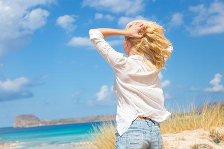 Entspannte Frau, die Freiheit und das Leben ein einen schönen Sandstrand genießen. Junge Dame, die das Gefühl frei, entspannt und glücklich. Konzept der Freiheit, Glücklichsein, Vergnügen und Wohlbefinden. Genießen Sonne auf Urlaub.