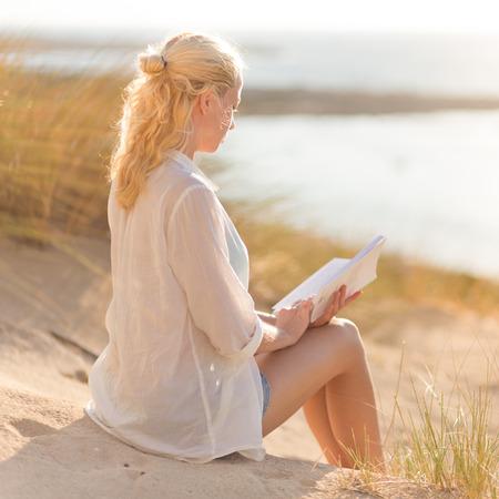 duna: Relajado mujer disfruta de la lectura en la hermosa playa de arena. Señora joven con el libro en la mano. Concepto de la felicidad, el disfrute y el bienestar. Disfrutando Sol en Vacaciones.