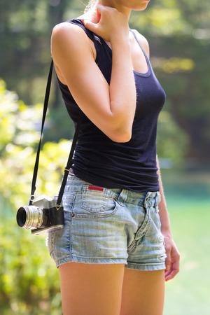 pantalones cortos: Hermosa niña caucásica rubia llevaba jeans cortocircuita un negro sin mangas de la camiseta deportiva, al aire libre en la naturaleza, llevar cámara de la vendimia por encima del hombro. Estilo de vida saludable y activo.