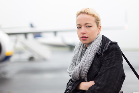 business traveller: Casually dressed young stylish female traveller boarding airplane in cold winter weather wearing winter coat and wool scarf. Woman on Business travel.