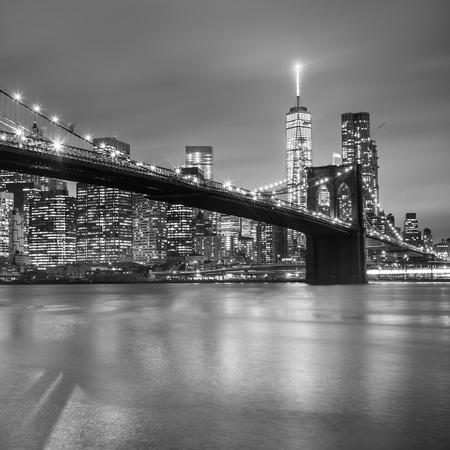 Brooklyn bridge and New York City Manhattan downtown skyline at dusk with skyscrapers illuminated over East River panorama. Copy space. Black and white image. Square image.