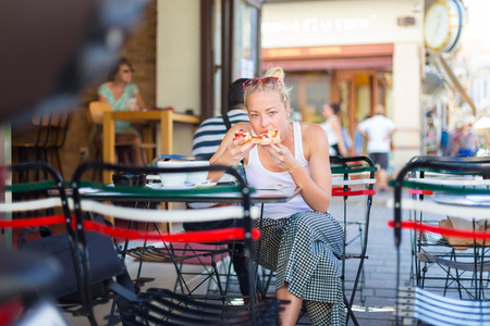 eating fast food: Casual blond lady eating pizza slice outdoor in typical italian street restaurant on hot summer day. Traditional italian fast food eatery.