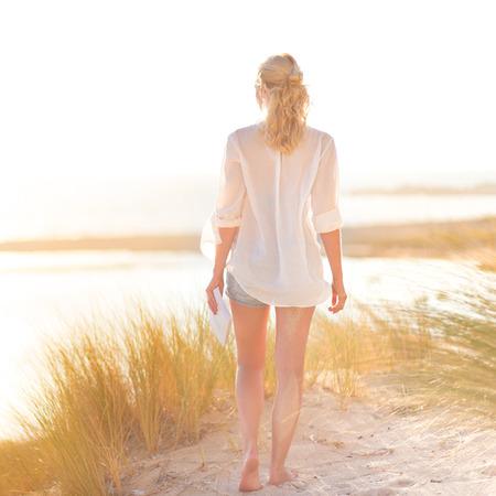 duna: Mujer relajada disfrutando de la libertad y de la vida de una hermosa playa de arena. Señora joven que se siente libre, relajado y feliz. Concepto de la felicidad, el disfrute y el bienestar. Disfrutando Sol en Vacaciones. Cuadrado. Foto de archivo