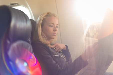 travel woman: Woman reading newspaper on airplane. Female traveler reading seated in passanger cabin. Sun shining trough airplane window.