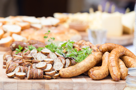 dry sausage: Dry sausage cold cuts. A variety of dry cold smoked meat products with herbs and mustard and  horseradish spreadon a wooden cutting board. Stock Photo