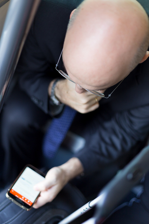 businessman waiting call: Businessmen using their cell phones on subway. Business travel and communication concept. view from above. Vertical composition. Stock Photo