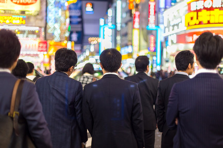 Japanese corporative business people in suits, waiting in rush hour on crossroad in Shinjuku business district, Tokyo, Japan. Blured advertising boards illuminated in the background.