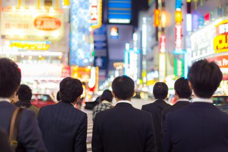gente trabajando: Los japoneses corporativos de negocios de traje, a la espera de la hora punta en la encrucijada en el distrito financiero de Shinjuku, Tokio, Japón. Carteles publicitarios Blured iluminados en el fondo. Foto de archivo