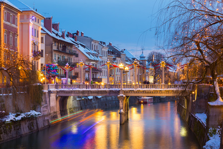 View of lively river Ljubljanica bank with Cobblers Bridge in old city center decorated with Christmas lights. Ljubljana, Slovenia, Europe. Shot at dusk.