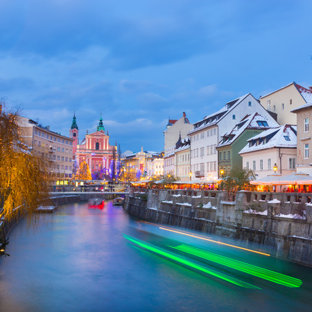 europe: View of lively river Ljubljanica bank and Tromostovje in old city center decorated with Christmas lights at dusk. Ljubljana, Slovenia, Europe.