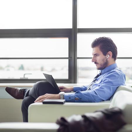audifonos: Retrato de joven empresario de éxito en la luminosa oficina moderna se centró en el trabajo en su computadora portátil el uso de auriculares. Vista lateral. Asunto y concepto de la iniciativa empresarial.