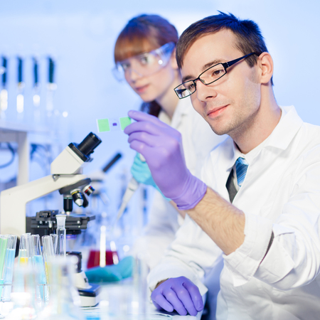 microscope slide: Young male researcher looking at the microscope slide in the laboratory of biotechnology . Forensics, microbiology, biochemistry, genetics, oncology..