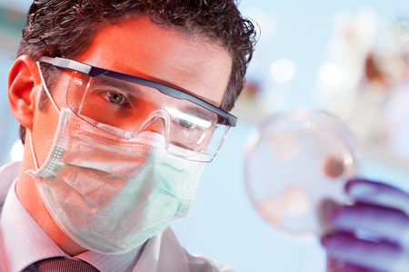 scientist: Mask protected life science professional observing the petri dish. Focus on scientists eye.