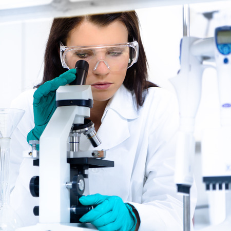 microscope slide: Attractive young PhD student scientist looking at the microscope slide in the life science research laboratory. Biochemistry, genetics, forensics, microbiology ..