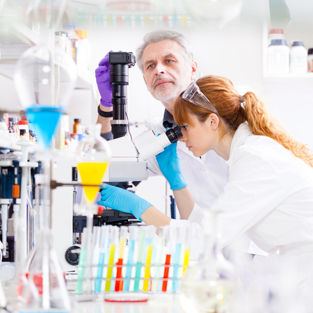 Attractive young female scientist and her senior male supervisor looking at the microscope slide in the life science research laboratory. Bichemistry, genetics, forensics, microbiology... Stock Photo
