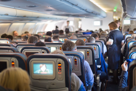 Interior of big commercial airplane with passengers on seats during flight. Stewardess in blue uniform walking the aisle, serving meal to people. Horizontal composition.