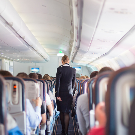 Interior of airplane with passengers on seats during flight. Stewardess in dark blue uniform walking the aisle. Square composition.