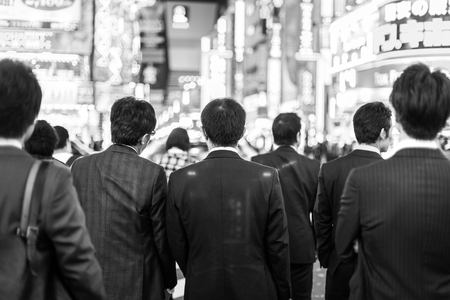 corporative: Japanese corporative business people in suits, waiting in rush hour on crossroad in Shinjuku business district, Tokyo, Japan. Blured advertising boards illuminated in the background. Black and white.
