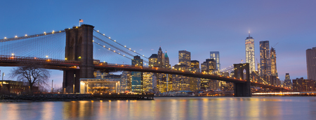brooklyn bridge: Brooklyn bridge and New York City Manhattan downtown skyline at dusk with skyscrapers illuminated over East River panorama. Stock Photo