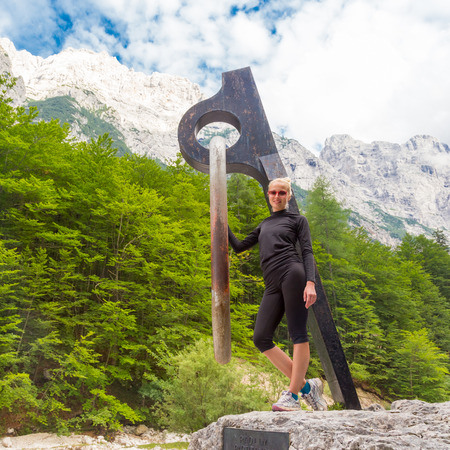 treck: Active sporty woman relaxing in beautiful natural mountain environment by statue of mighty piton, monument to victims of mountains in Vrata Valley in Triglav National Park in Julian Alps, Slovenia. Stock Photo