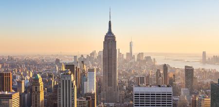 Nueva York. Horizonte de la ciudad de Manhattan con iluminación Empire State Building y rascacielos al atardecer visto desde la parte superior de la plataforma de observación Rock. Composición vertical.