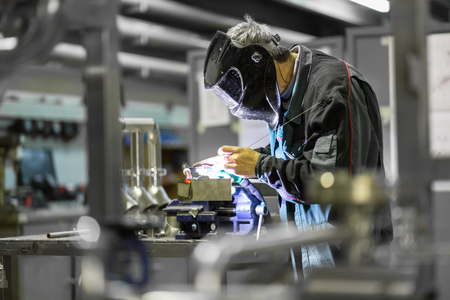 skilled: Industrial worker with protective mask welding inox elements in steel structures manufacture workshop. Stock Photo