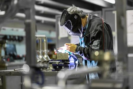 Industrial worker with protective mask welding inox elements in steel structures manufacture workshop. Standard-Bild