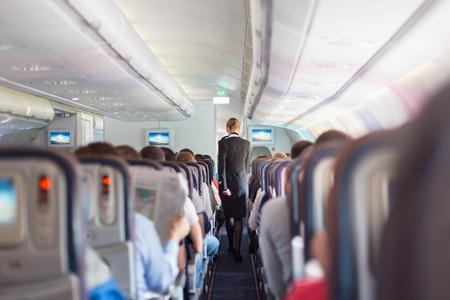 cabaña: Interior del avión comercial de pasajeros en los asientos durante el vuelo. Azafata en uniforme azul oscuro caminando por el pasillo. Composición horizontal.