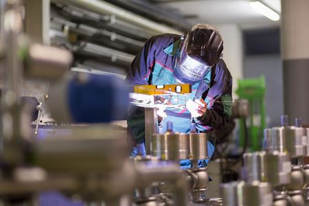 factory: Industrial worker with protective mask welding inox elements in steel structures manufacture workshop. Stock Photo