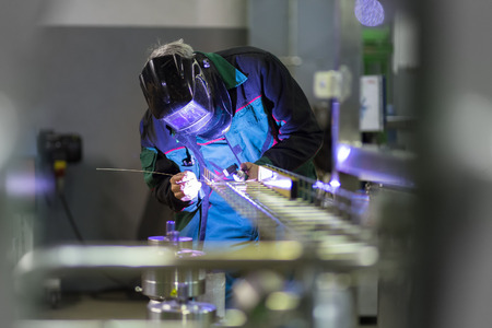 Industrial worker with protective mask welding inox elements in steel structures manufacture workshop. Stockfoto