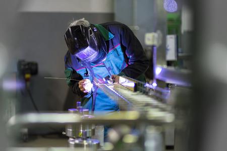 Industriearbeiter mit Schutzmaske Schweißen inox Elemente in Stahlkonstruktionen fertigen Werkstatt.