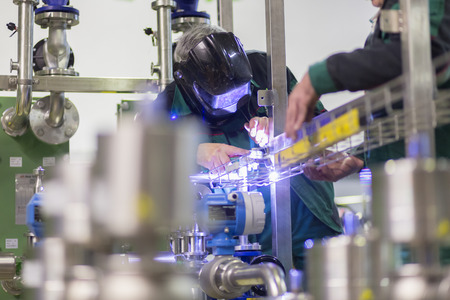 skilled labour: Industrial worker with protective mask welding inox elements in steel structures manufacture workshop. Stock Photo